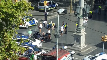 Injured are helped by responders after a white van jumped the sidewalk in the historic Las Ramblas district of Barcelona.