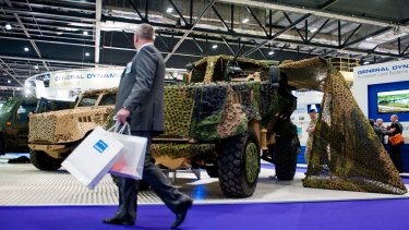 A visitor walks past the General Dynamics pavilion during the 2013 edition of the DSEI arms fair in London.