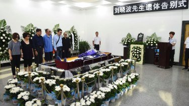 Relatives stand next to the casket of Chinese dissident Liu Xiaobo during his funeral on Saturday.