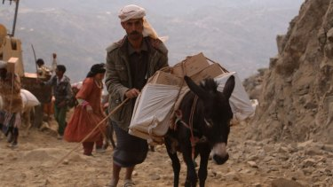 A man carries food across the mountain to cut-off areas of the Yemeni city of Taiz.
