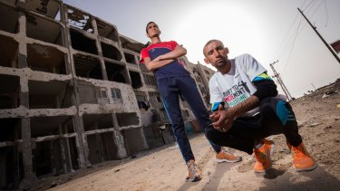 Nader al-Masri (right) and Anas al-Masri  outside a building destroyed by Israeli bombardment in the Gaza Strip town of Beit Hanoun.