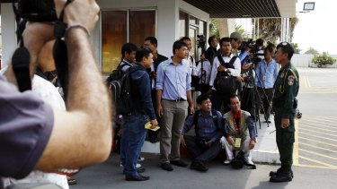 Journalists wait for the transportation of refugees last year from Phnom Penh International Airport to the accommodation Australia arranged for them.