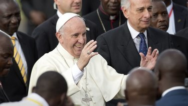 Pope Francis greets traditional dancers on his arrival at the airport in Nairobi, Kenya.
