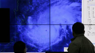 Government meteorologists look at a satellite image of Typhoon Melor in the weather bureau centre in suburban Quezon city, northeast of Manila.