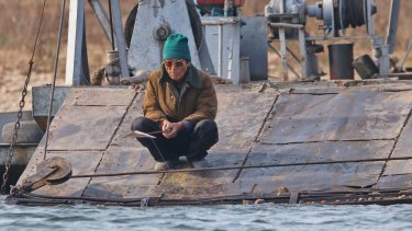 A North Korean man fishes off a ferry in Sinuiju near the Chinese border.