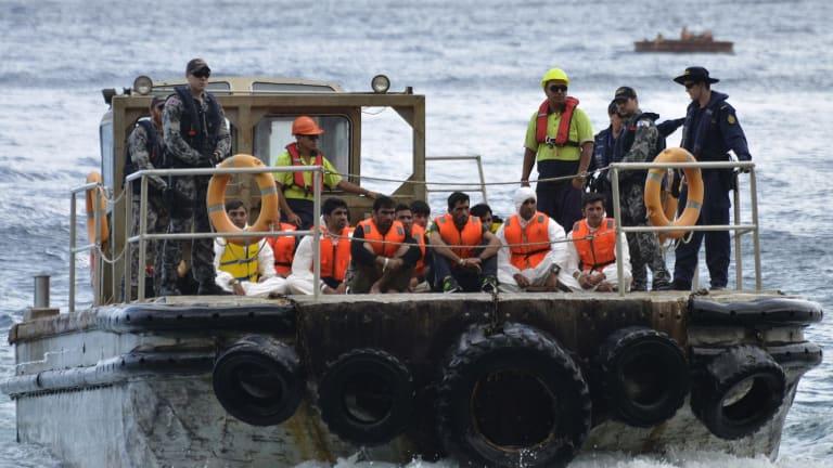 Australian Customs officials and navy personnel escort asylum seekers to Christmas Island.