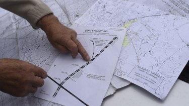 Tadeusz Slowikowski, a local explorer, points on map of the area where a tunnel with a Nazi train is believed to be.