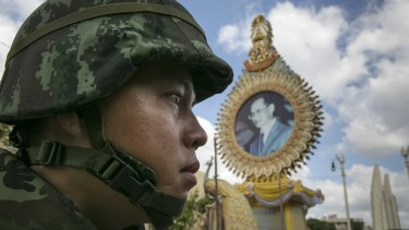 A Thai soldier patrols near government buildings in front of a portrait of King Bhumibol Adulyadej in May.