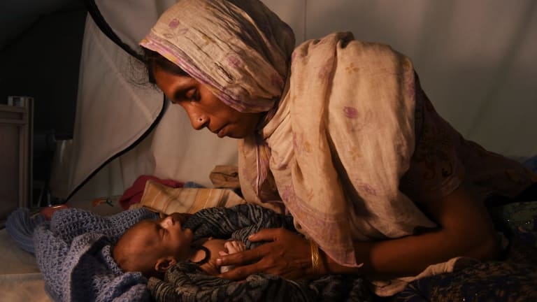 Laila Begum holds her son Ifran's hand as he receives treatment in a Red Cross hospital tent at a Rohingya refugee camp in Bangladesh.