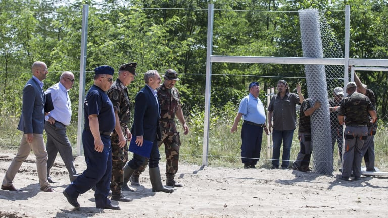 Hungarian ministers inspect the first portion of the fence.