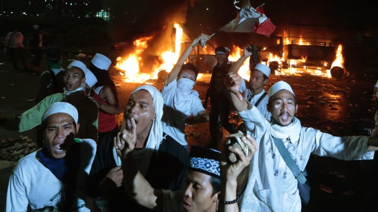 Muslim protesters chant slogans near burning police trucks.