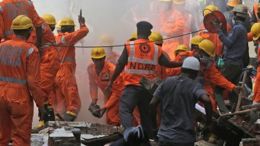 Rescuers work at the site of a building collapse in Mumbai, on Thursday.