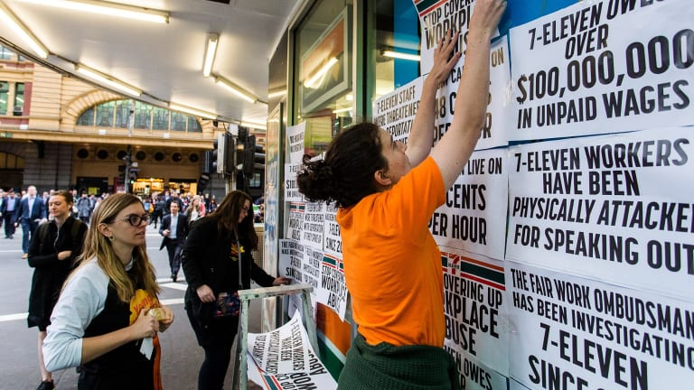 Protestors from the Young Workers Centre pin signs to the windows of 7-Eleven on the corner of Elizabeth and Flinders Street in Melbourne.