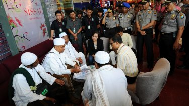 Police look on at a Surabaya shopping centre as centre staff sign a document promising not to dress employees in Christmas apparel.