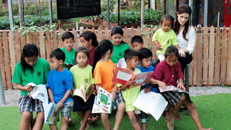 """Australian Tara Winkler from the Cambodian Children's Trust with students in Cambodia. Ms Winkler campaigns to stop so-called """"orphan tourism""""."""