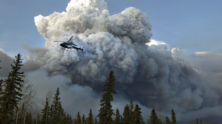 A helicopter flies past a wildfire in Fort McMurray, Canada