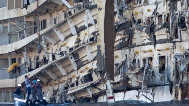 Workers inspect the wreck of the Costa Concordia after it was righted in September 2013.