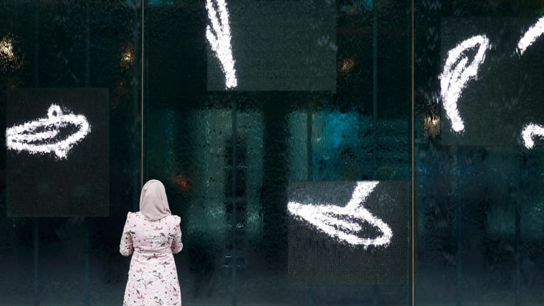 A visitor watches fish swimming at the waterwall entrance to NGV International.