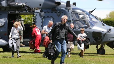 Tourists trapped by the Kaikoura earthquakes arrive by military helicopters at Woodend School grounds in Christchurch on Tuesday.