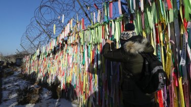 A visitor takes a photo near the North-South Korea border fence decorated with ribbons carrying messages to wish for the reunification of the two Koreas at the Imjingak Pavilion in Paju, South Korea.