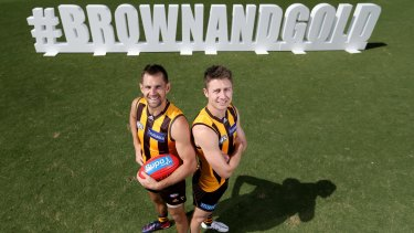 Hawthorn captain Luke Hodge and Liam Shiels in front of a promotional sign that supporters can take photos with before Monday's Hawthorn-Geelong game at the MCG.