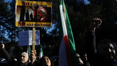 "An Iranian opposition supporter holds up a placard bearing a picture of President Hassan Rouhani that reads ""No to Rouhani no to executions"", during a protest outside the Iranian embassy in Rome."