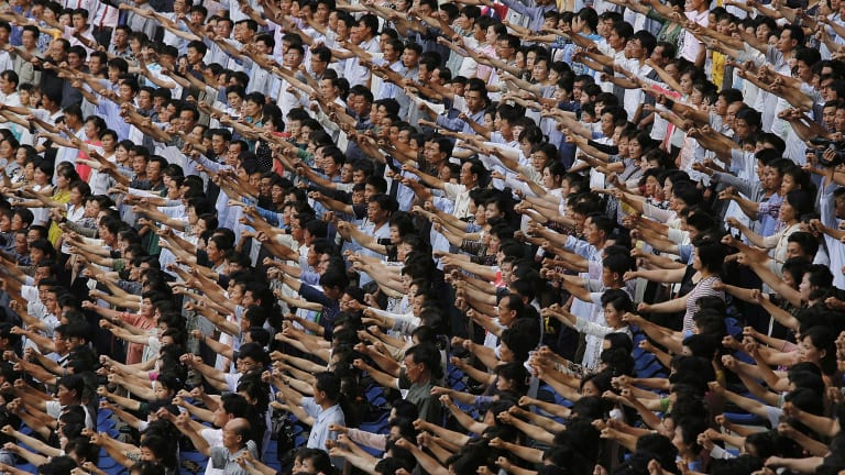 "Men and women pump their fists and chant ""Defend!"" as they carry propaganda slogans calling for reunification of their country during the ""Pyongyang Mass Rally on the Day of the Struggle Against the US,"" attended by approximately 100,000 North Koreans in June."