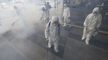 Antiseptic solution is sprayed in an attempt to halt the spread of MERS outside Wangsimni subway station in Seoul on Thursday.