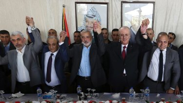 From left to right in front row, Hamas leader in the Gaza Strip Yahya Sinwar, Head of Palestinian General Intelligence Majid Faraj, Head of the Hamas political bureau Ismail Haniya, Palestinian PM Rami Hamdallah and an Egyptian mediator hold their hands up in Gaza City on Monday.