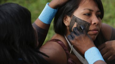 A Kayapo paints the face of her daughter during an assembly in Brasilia on Monday. Indigenous ethnic groups are in the capital to demand education, health and demarcation of indigenous lands.