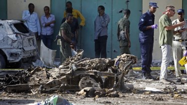 Somali soldiers stand near the wreckage of a car bomb in Mogadishu, Somalia, on December 19. Fears about Somalians in America link refugees to the wars and instability they fled.