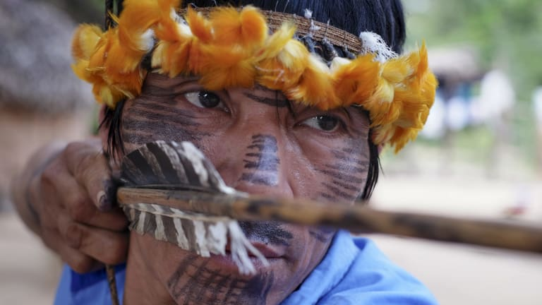A tribesman checks his bow and arrow in Awa Village, Brazil.