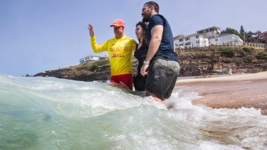 Volunteer lifesaver Paul Borrud teaches new Syrian refugees Alaa (Alan) Alnseer and his sister Lama about water safety at Tamarama.