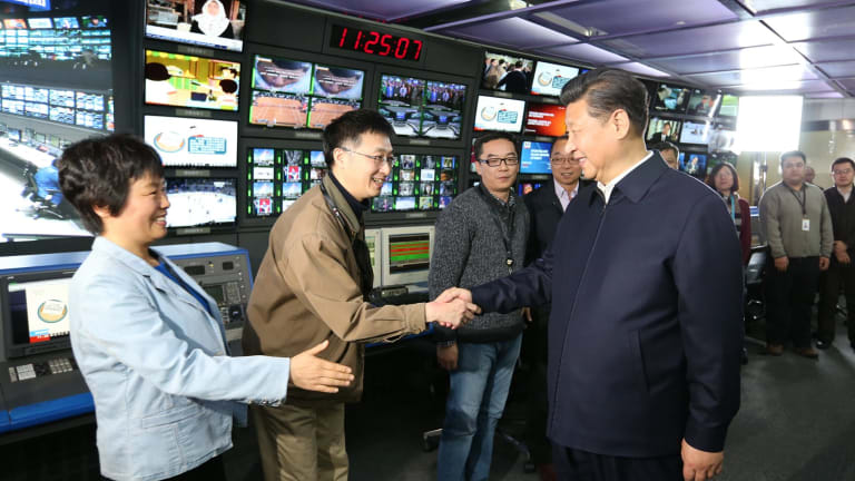 In this photo released by China's Xinhua News Agency, Chinese President Xi Jinping, right, shakes hands with staff members at the control room of China Central Television (CCTV) in Beijing in February.