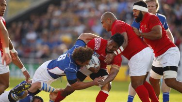 Tonga's Jack Ram is tackled by Namibian captain Jacques Burger.