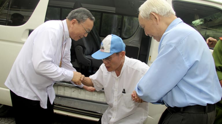 Catholic priest Nguyen Van Ly, centre, is welcomed back by Archbishop Tadeo, left, and a senior colleague to his parish in Hue, Vietnam.