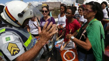 A policeman turns away a group of women hoping to join a march in Brasilia supporting a general strike, because the instruments they were carrying could be used as weapons.