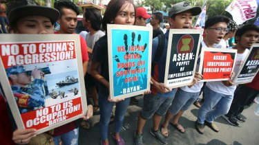 Protesters display placards at a rally near the venue in Manila.