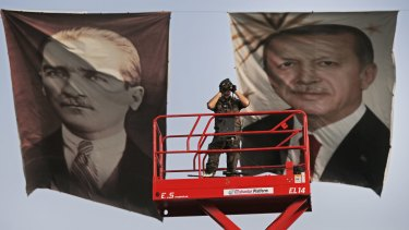 """A policeman stands between portraits of Turkish President Recep Tayyip Erdogan, right, and the republic's founder, Mustafa Kemal """"Ataturk""""."""