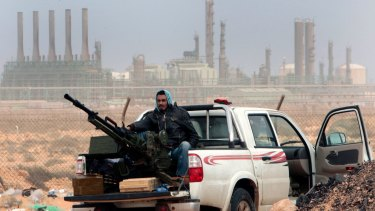 A rebel sits with an anti-aircraft weapon in front of an oil refinery in Ras Lanouf, eastern Libya.