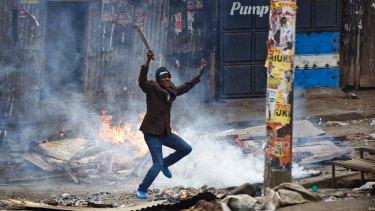 """A man brandishing a """"panga"""" machete challenges policee in the Mathare slum of Nairobi."""