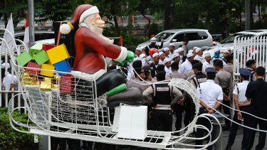A Santa on a sleigh is seen near a protest against Christmas apparel by members of the hardline Islam Defenders Front in Surabaya.