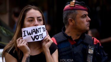 A demonstrator covers her mouth next to a Catalan police officer in Barcelona.