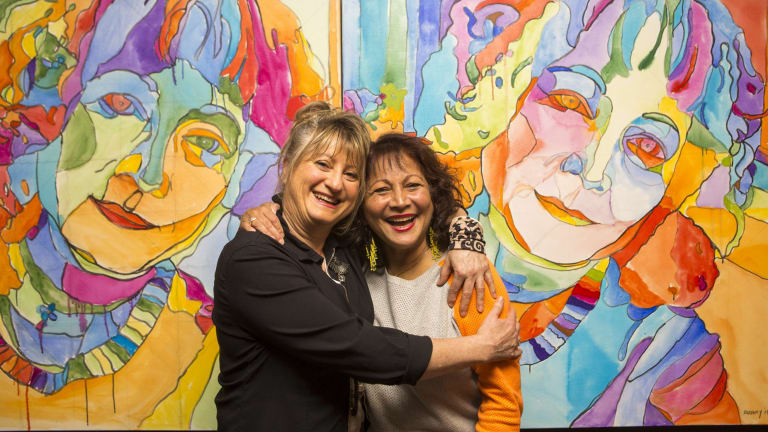 Childhood friends Beverley Pinder (left) and Rachel Rovay pose for a photo in front of a portrait of Beverley painted by Rachel for the Archibald competition.