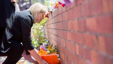 Ardent Leisure chief executive Deborah Thomas places flowers at the memorial at the Dreamworld gates.