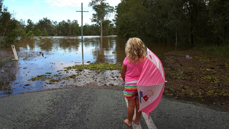 Chloe Nelson, 5, looks out at flood water near her home outside Jimboomba.