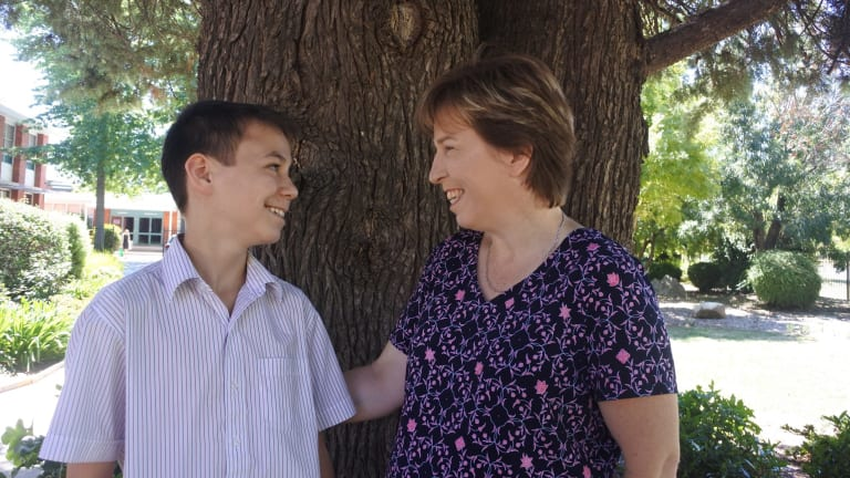 Daramalan College student Dylan Joe, 13, with his mum Jill Pareezer. Dylan, who cares for his mum who has disabilities, has been chosen to turn on the lights at Enlighten.