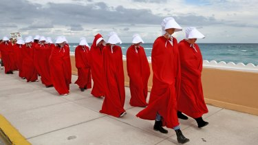 Protester dressed as handmaidens from <i> The Handmaid's Tale</i> march in protest of Donald Trump in West Palm Beach, Florida.