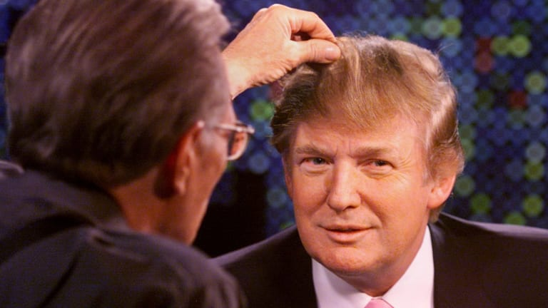 Talk show host Larry King examines Trump's hair in 2004.