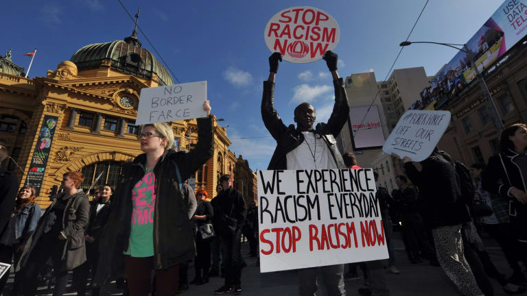 Demonstrators protesting against planned border protection raids stop traffic outside Flinders Street Station on Friday.